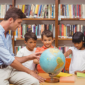 Children and their teacher looking at a world globe.
